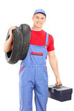 Male mechanic carrying tires and holding toolbox Stock Photo