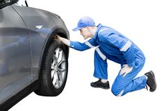 Male mechanic checking a flat tire on studio. Image of young male mechanic checking a flat tire of a car, isolated on white background Royalty Free Stock Photo