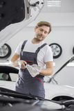 Male mechanic checking oil in car workshop Royalty Free Stock Photos