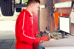 Male mechanic checking the readout on a computer. Hooked to a car elevated on a hoist as he performs a service and tune up in a garage workshop Royalty Free Stock Image