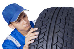 Male mechanic checking a tire Stock Photography