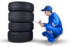 Male mechanic checks a pile of tires. Young technician with a blue uniform examining a pile of tires and write the report at the clipboard Royalty Free Stock Photos