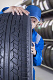 Male mechanic checks a tire seriously Royalty Free Stock Images