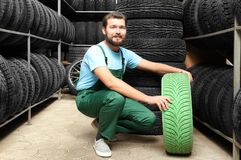 Male mechanic with color car tire. In automobile store Royalty Free Stock Images