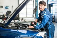 Male Mechanic Filling Oil Into Car's Engine At Garage Royalty Free Stock Photo