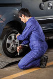 Male Mechanic Fixing Car Tire At Repair Shop Royalty Free Stock Photography