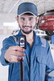 Male mechanic gives a car key in workshop Royalty Free Stock Images