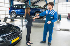 Male Mechanic Giving Car Key To Client After Servicing Stock Photos
