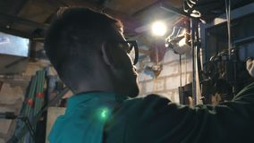 Male mechanic in glasses fixes car detail. Man in workwear works in garage or workshop. Hard work concept.Slow motion