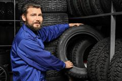 Male mechanic holding car tire. In automobile store Royalty Free Stock Photography