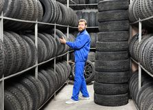 Male mechanic holding car tire. In automobile store Stock Photography