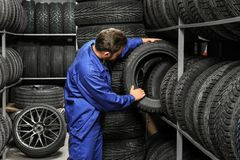 Male mechanic holding car tire. In automobile store Stock Photos