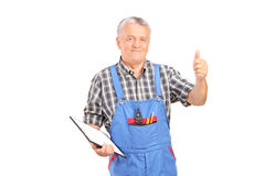 Male mechanic holding clipboard and giving thumb up Stock Image
