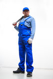 Male mechanic holding monkey wrench on white Stock Photography