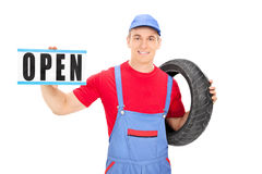 Male mechanic holding an open sign Stock Image