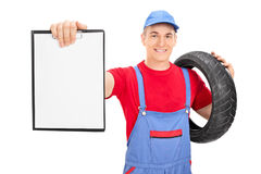 Male mechanic holding a tire and a clipboard Royalty Free Stock Photography