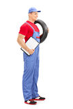 Male mechanic holding a tire and a clipboard Stock Images