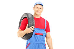 Male mechanic holding a vehicle tires and looking at camera Stock Photography