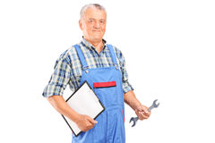 Male mechanic holding a wrench and a clipboard. Isolated against white background Royalty Free Stock Images