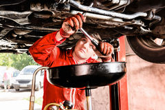 Male mechanic hooking up equipment to the undercarriage of a car. Elevated on a hoist during repairs and maintenance in a garage workshop Royalty Free Stock Photography