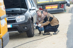 Male mechanic inflating car tire near female client Royalty Free Stock Images
