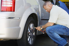 Male Mechanic Inflating RV Tire. Side view of a male mechanic inflating RV tire Stock Images