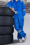 Male mechanic lean on tires in the garage. Mechanic person with blue uniform, standing in the workshop while holding a wrench and leans on tires Stock Photography