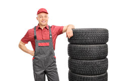 Male mechanic leaning on a stack of tires Stock Image