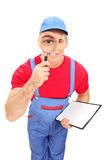 Male mechanic looking through magnifying glass Royalty Free Stock Image