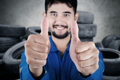 Male mechanic with old tires. Close up of middle eastern mechanic showing two thumbs up and standing with stacks of old tires Stock Image