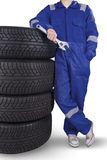 Male mechanic and pile of tires. Male mechanic holding wrench while leaning with pile of tires in the studio Royalty Free Stock Photo