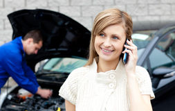 Male mechanic repairing the car of a busy woman Stock Image