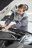 Male mechanic repairing car engine in workshop Stock Photos
