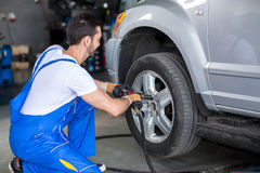 Male mechanic repairing car's wheel Royalty Free Stock Photography