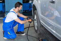 Male mechanic repairing car wheel Royalty Free Stock Image