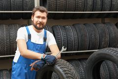 Male mechanic with spanner and car tire. In automobile shop Royalty Free Stock Images