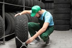 Male mechanic with spanner and car tire. In automobile store Stock Photos