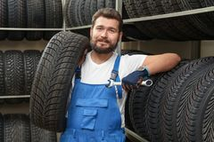 Male mechanic with spanner and car tire. In automobile shop Stock Photo