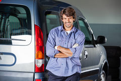 Male Mechanic Standing Arms Crossed By Car. Portrait of smiling male mechanic standing arms crossed by car at repair shop Stock Image
