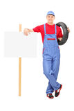 Male mechanic standing next to a blank sign Stock Images