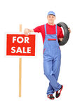 Male mechanic standing by a for sale sign Stock Images