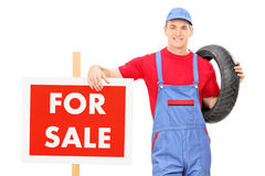 Male mechanic standing by a for sale sign Stock Photo