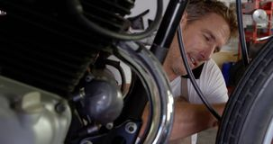 Male mechanic talking on mobile phone while repairing motorbike in garage 4k. Front view of Caucasian male mechanic talking on mobile phone while repairing stock footage