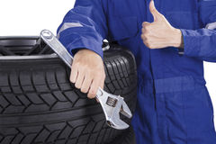 Male mechanic with tire and wrench. Close up of male mechanic giving thumb up and holding a wrench while leaning with tires Royalty Free Stock Photos