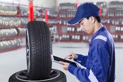 Male mechanic with tires and tablet Stock Photos