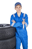 Male mechanic with tires and wrench. Portrait of a car mechanic wearing uniform and holding a wrench while standing near the tires Royalty Free Stock Photo
