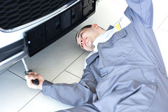 Male mechanic under car. Male mechanic under the car Stock Photo