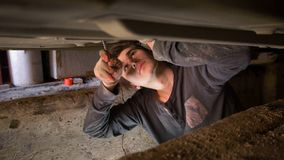 Male mechanic underneath a car working on the repair of the car royalty free stock image