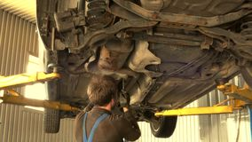 Male mechanic unscrew car bottom protection bolts. Man working under lifted auto with spanner tool stock video footage