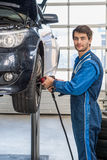 Male Mechanic Using Pneumatic Wrench To Fix Car Tire Royalty Free Stock Images